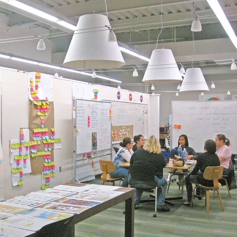 Visual communication design students meet in a collaborative workspace.