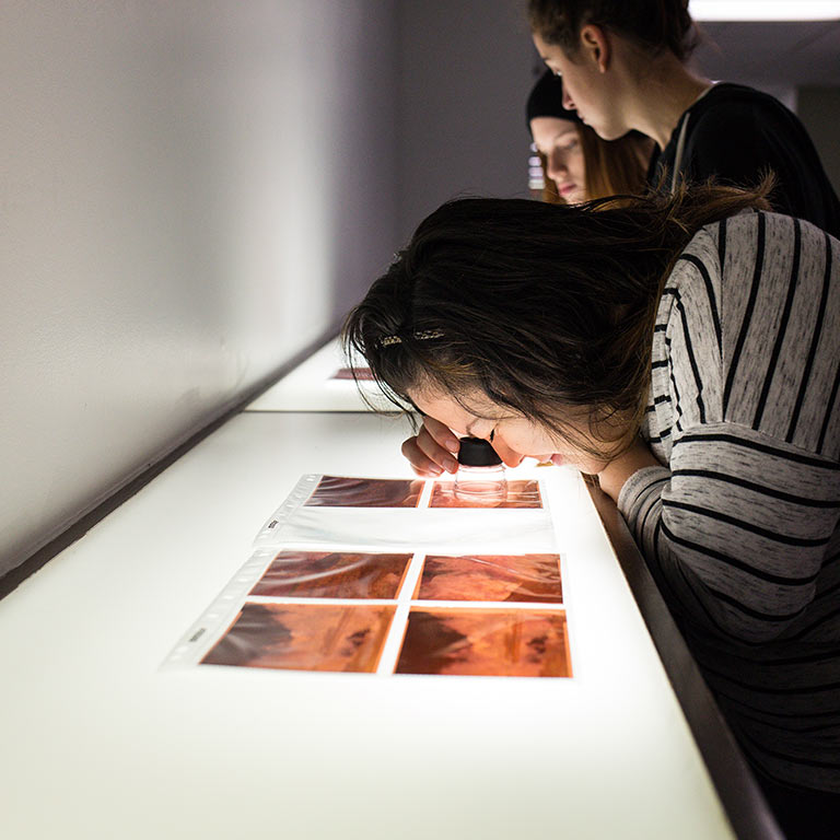 Photo students view prints on a light box.