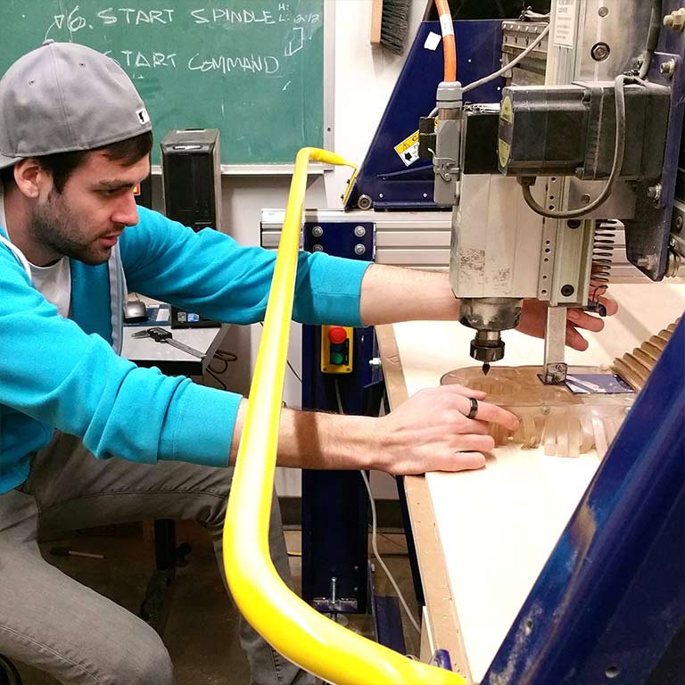 A male student uses a CNC machine to carve a piece of furniture in the Think It Make It Lab.