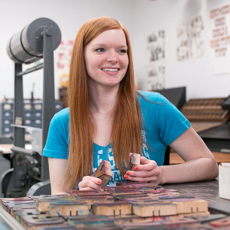 A student smiles as she works with letterpress.
