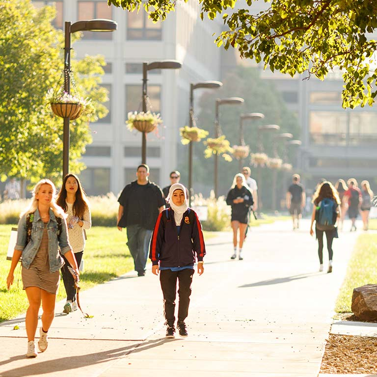 Students walk through campus on a sunny afternoon.