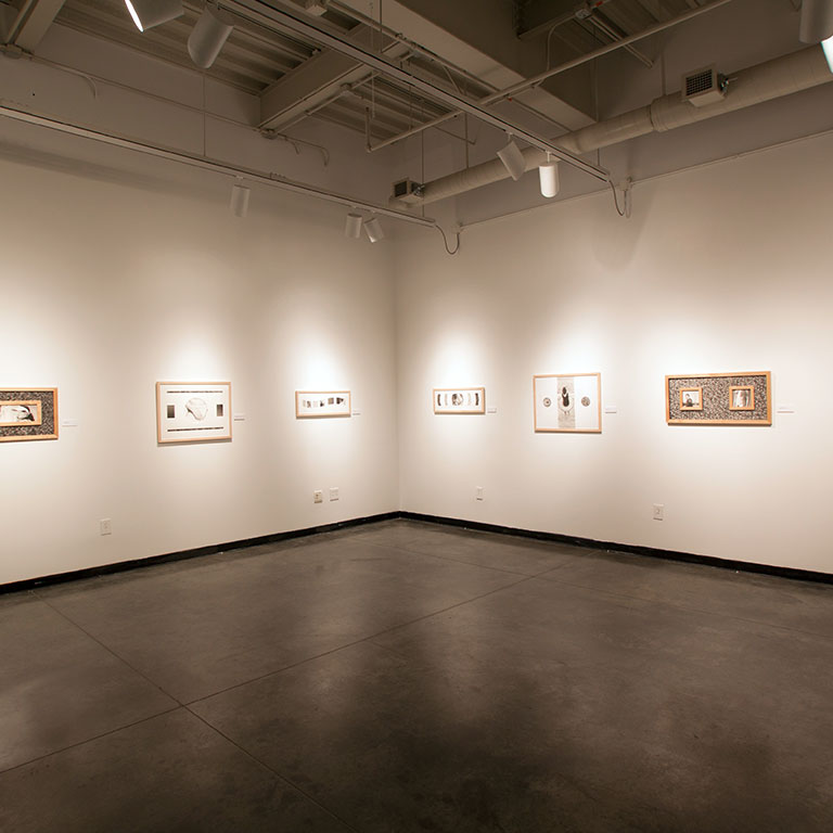 A gallery space with black floors, white walls, and frames hanging on the walls.