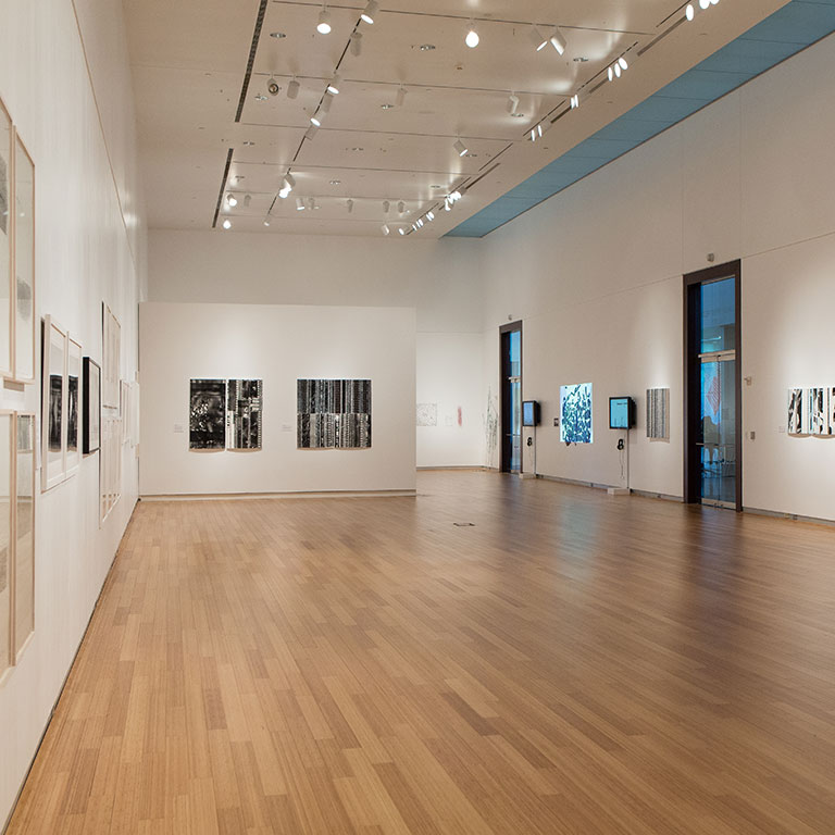 A gallery space with wood floors, tall ceilings, and plasma TVs installations on the walls.