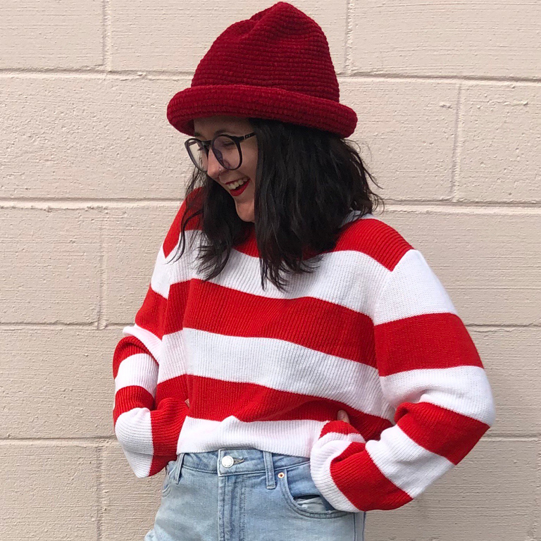 "A smiling Madison Rose wearing a ""Where's Waldo?"" style outfit."