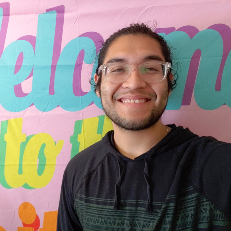 A selfie of Juan Villalva smiling in front of a colorful backdrop.